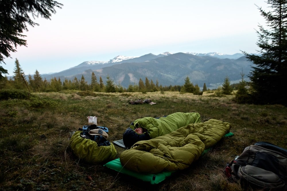 Man sleeping alone in a sleeping bag in the woods