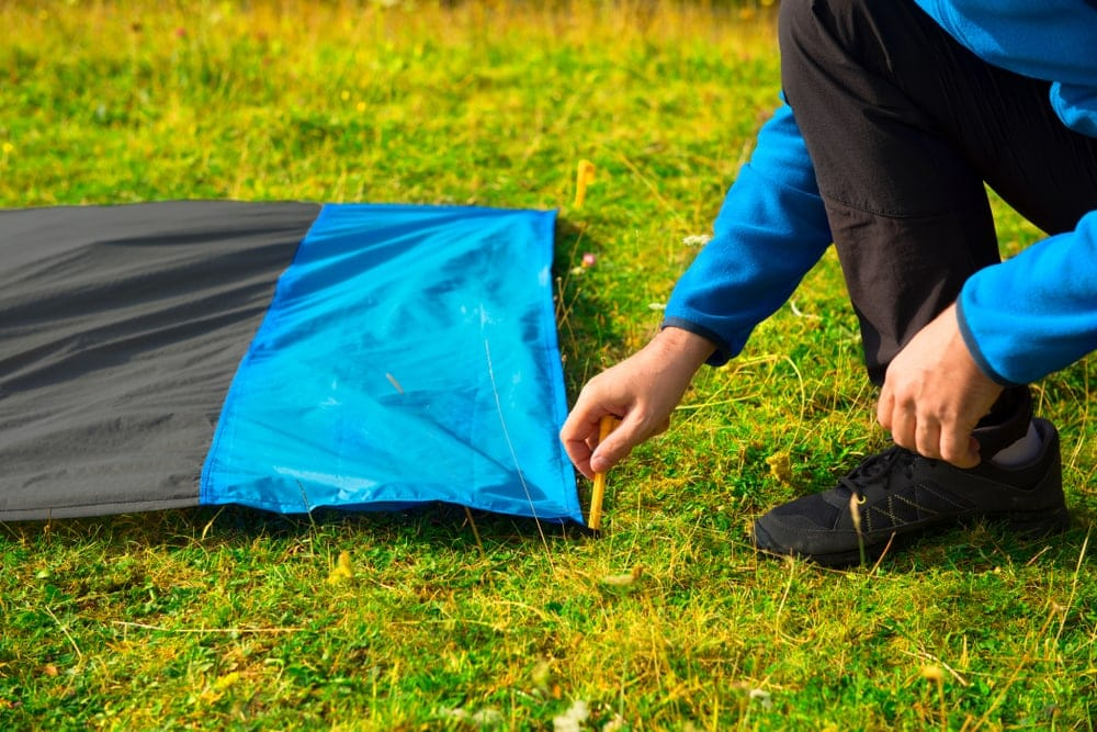 Man setting up a camping footprint for additional safety when cowboy camping