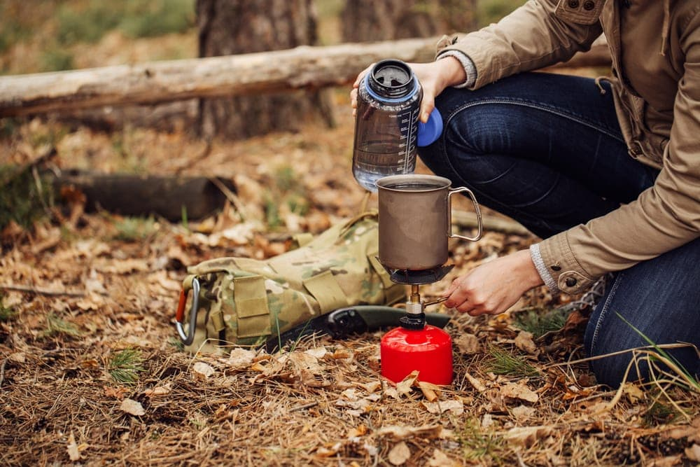 A hiker pouring water on an empty big camping mug