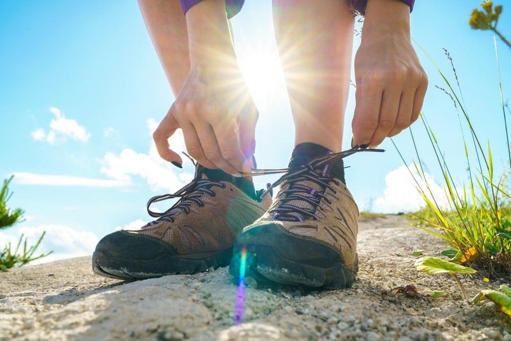 Hiker tying her hiking shoelaces