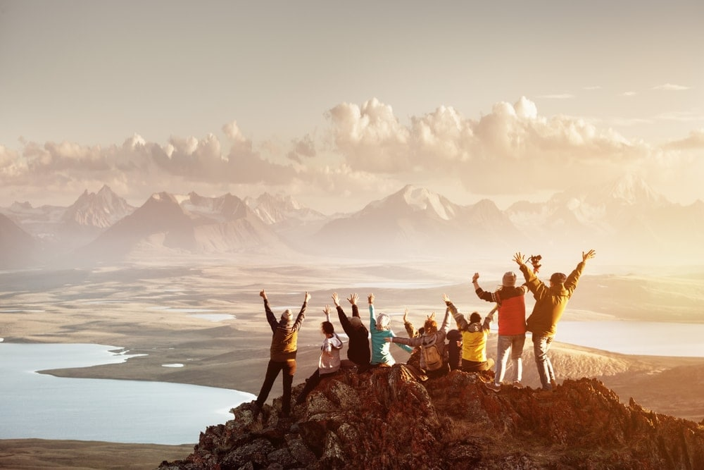 Large group of hikers enjoying the view on top of a mountain