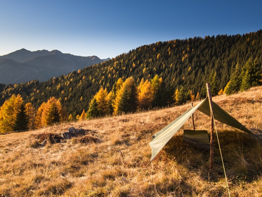 A simple tarp shelter on a hill with autumn trees in the background