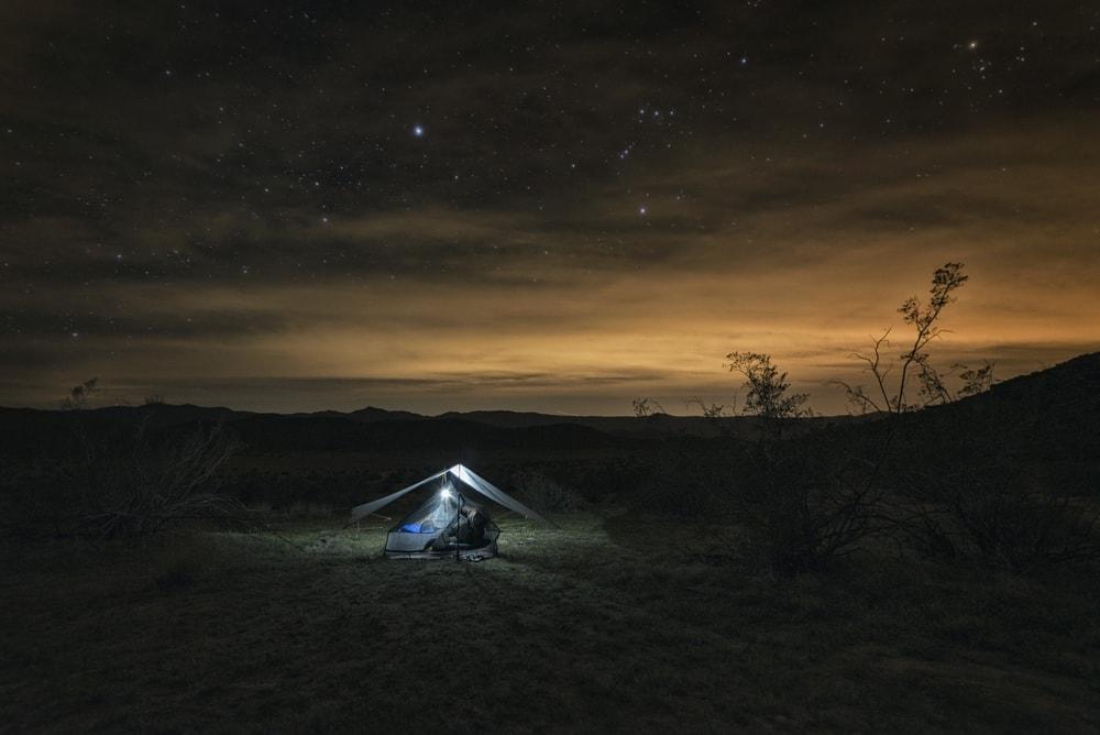 Tarp shelter set up on a flat ground under starry night sky