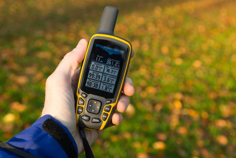 Person's hand holding a handheld gps for hiking