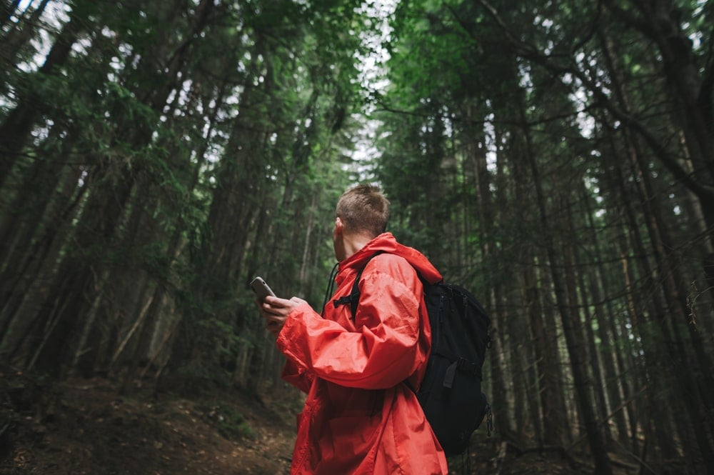 Hiker in a red jacket using a smartphone gps and looking around in the woods