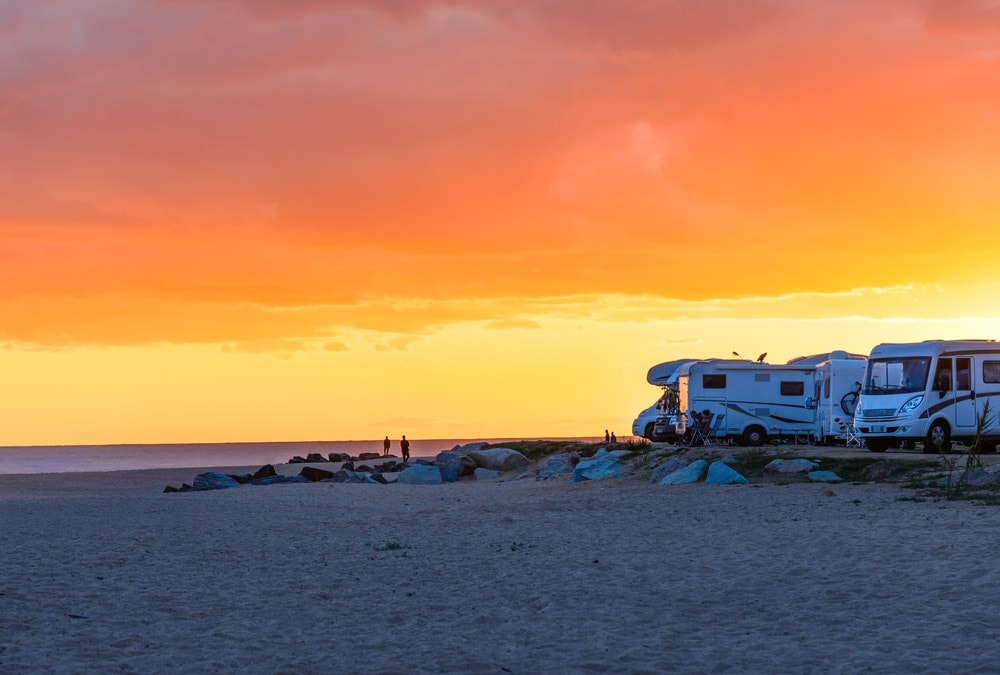 Campers on the beach during a summer sunset