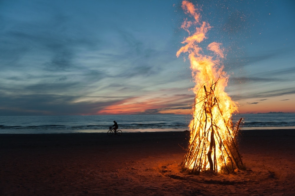 Big bonfire on a beach with man bicycling in the background