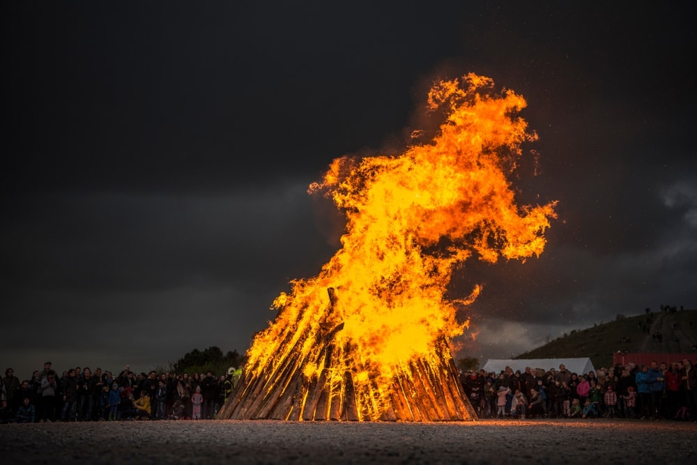 High and big bonfire surrounded by people