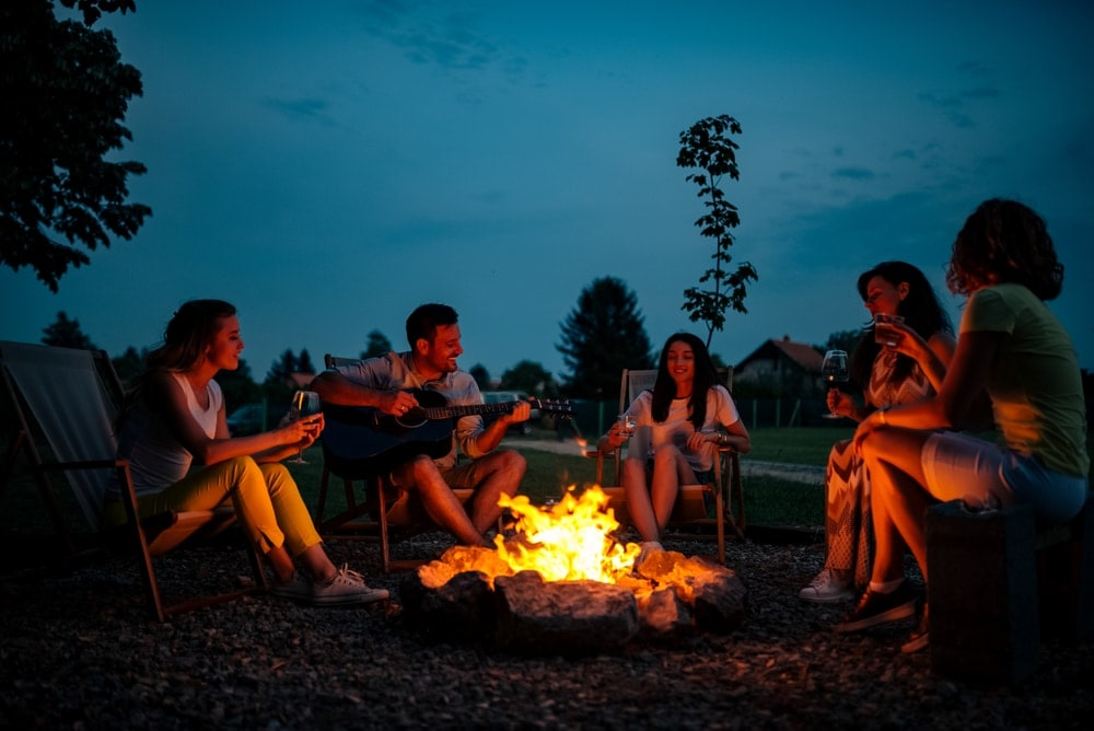 Group of friends singing around a campfire