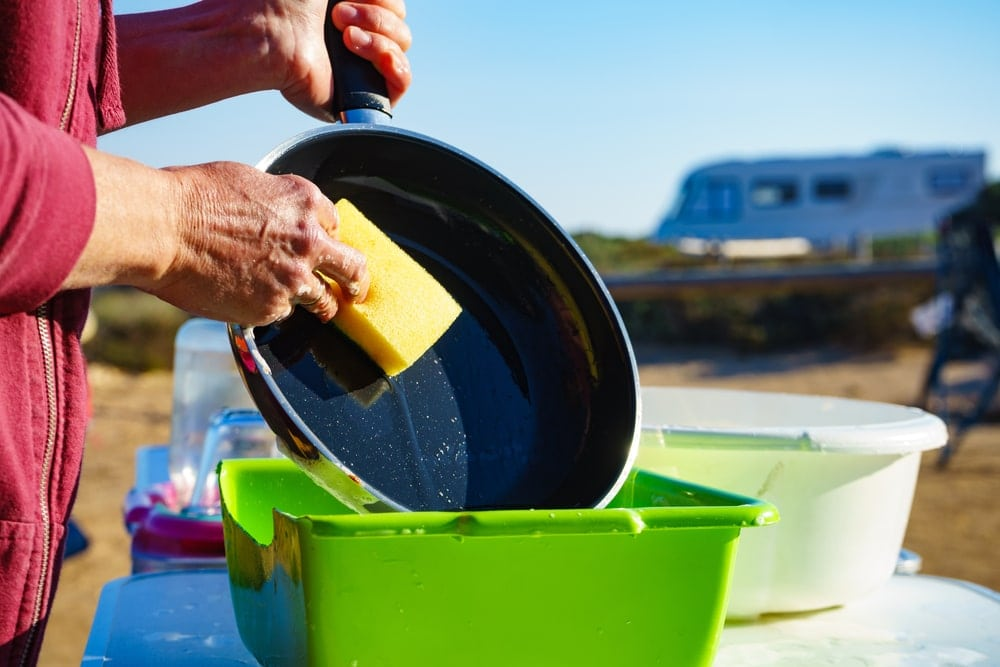 Woman washing up dishes in the campsite