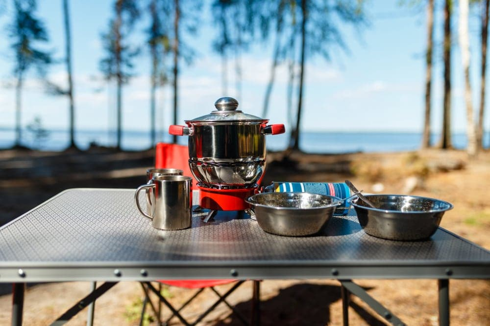 Cooking pans on fire from a portable gas burner next to plates and mugs on a camping table