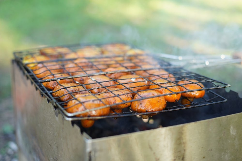 Mushrooms  being cooked in a camping basket grill