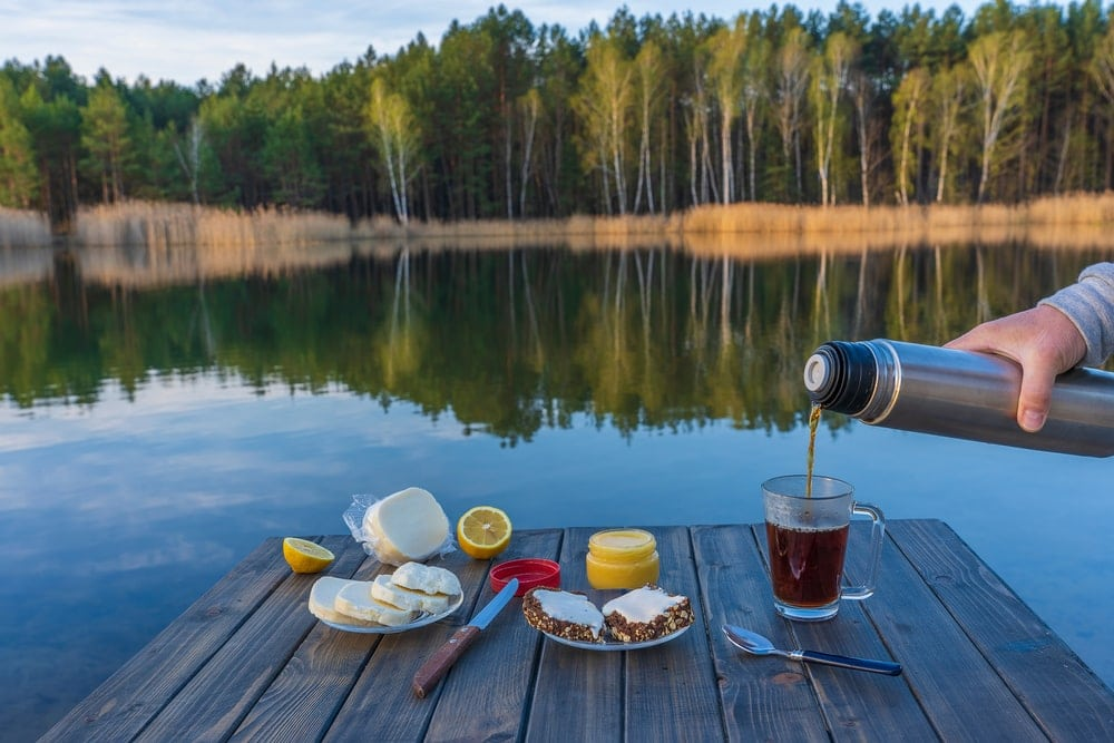 A person pouring coffee to a glass mug next to a camping breakfast on a wooden table