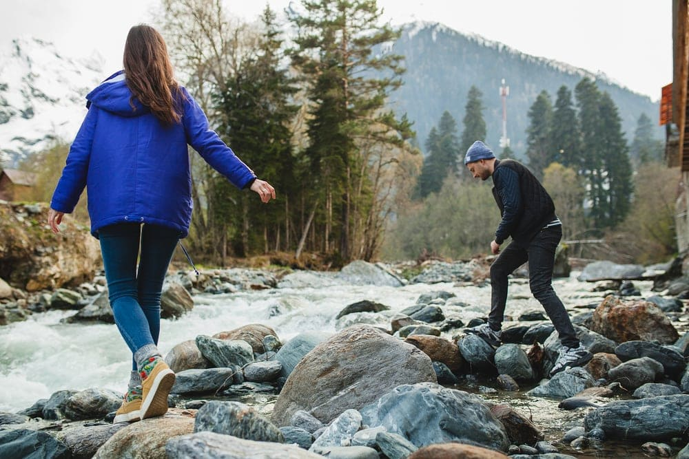 Beautiful couple hiking on rocks at river in winter forest
