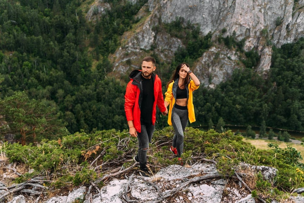 Couple are holding hands while hiking