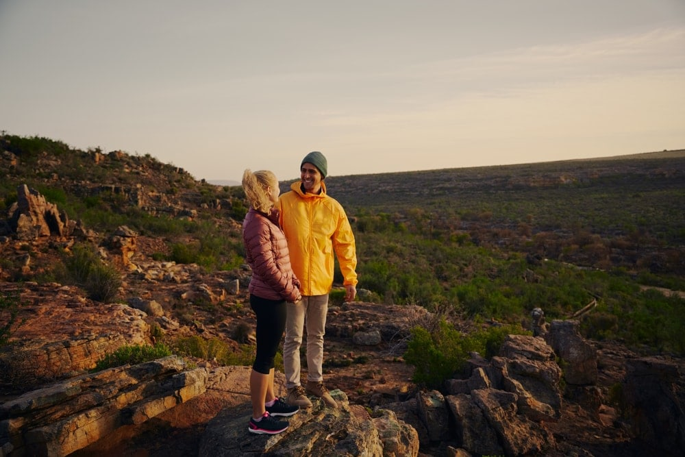 Man and woman smiling at each other on a hiking date