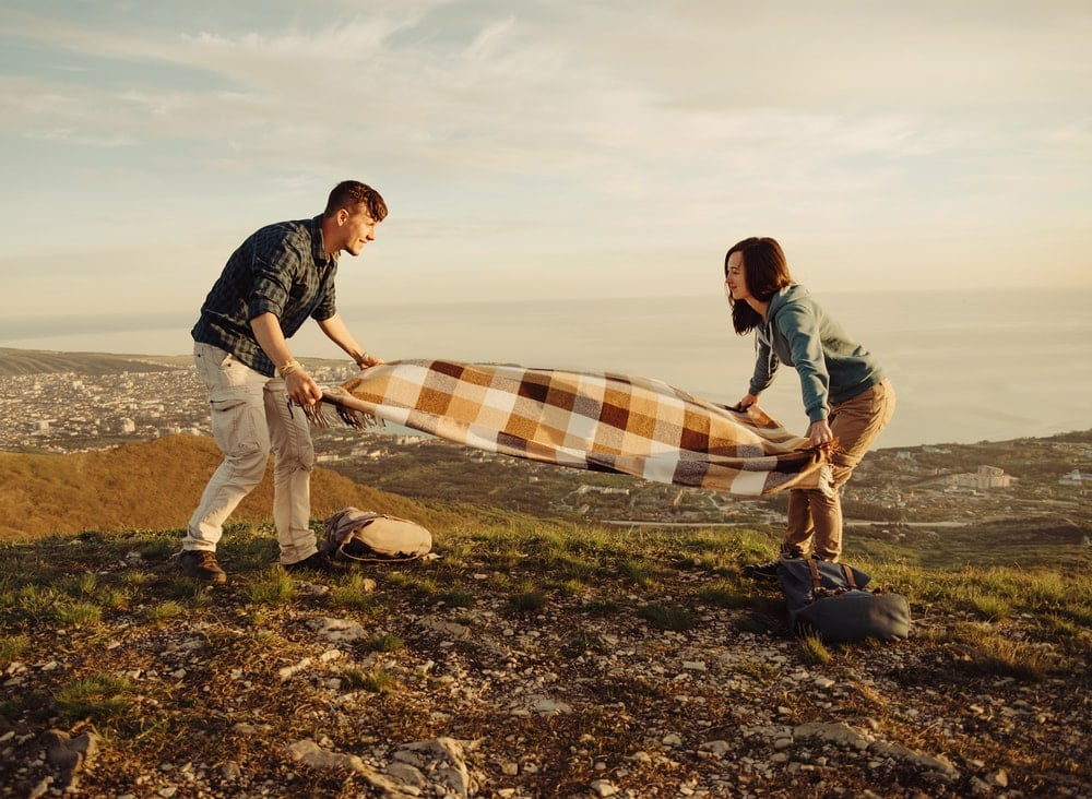 Couple spreading a blanket on a hill after hiking