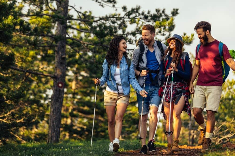 2 couples laughing while hiking on the woods