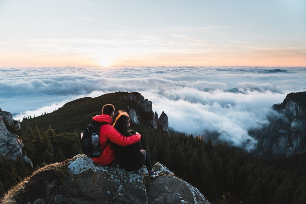Couple on top of the mountain watching together the sea of clouds after hiking