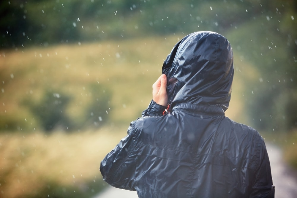 Hiker holding a hiking jacket during a rain