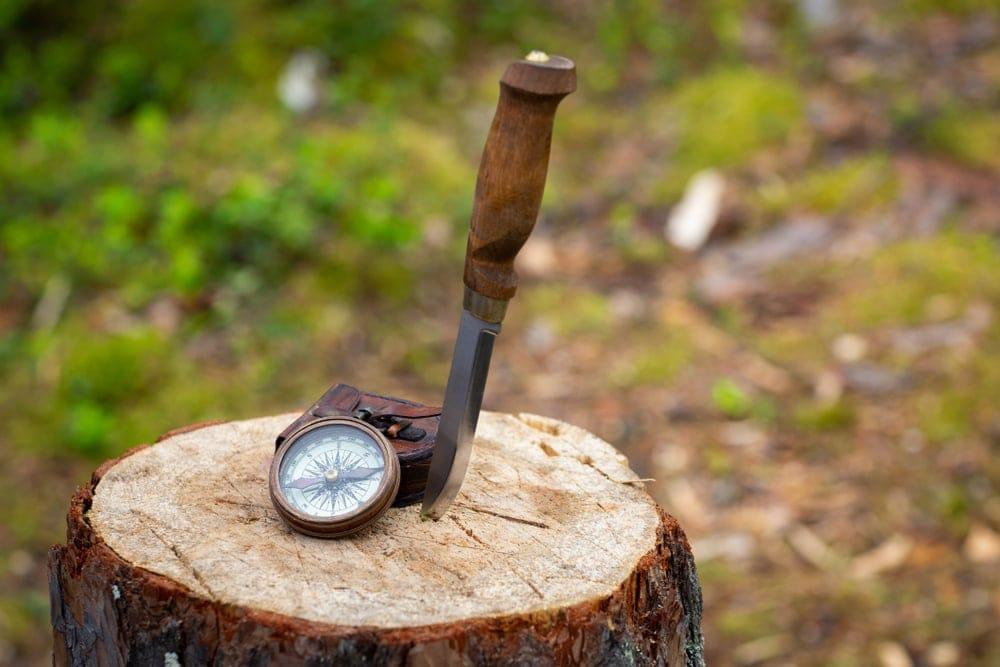 A hiking knife and a compass on a tree stump
