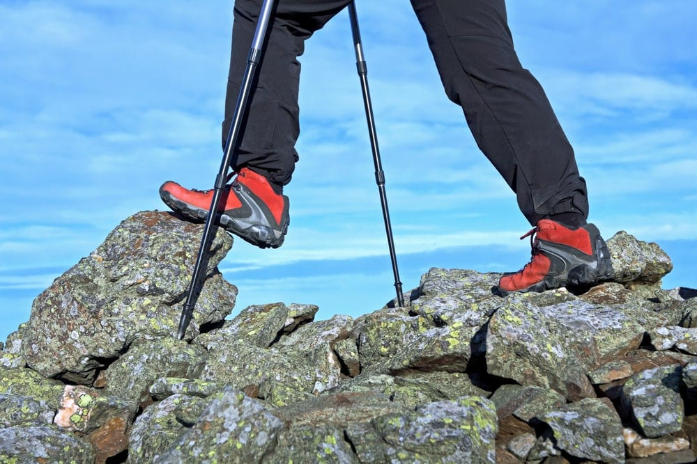 Hiking on rocks with a hiking shoes and trek poles