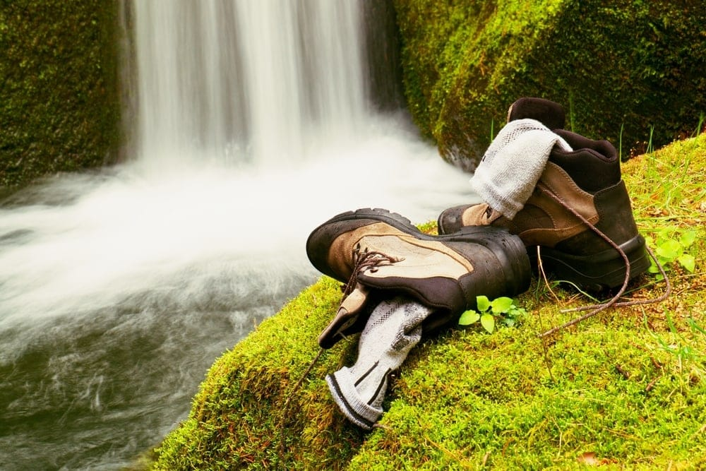 A pair of  hiking socks in the shoes facing a waterfall