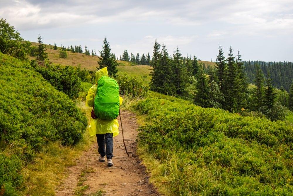 Hiker wearing a rain poncho on the trail