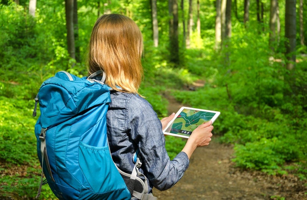 A woman holding a large screen GPS for navigation while hiking