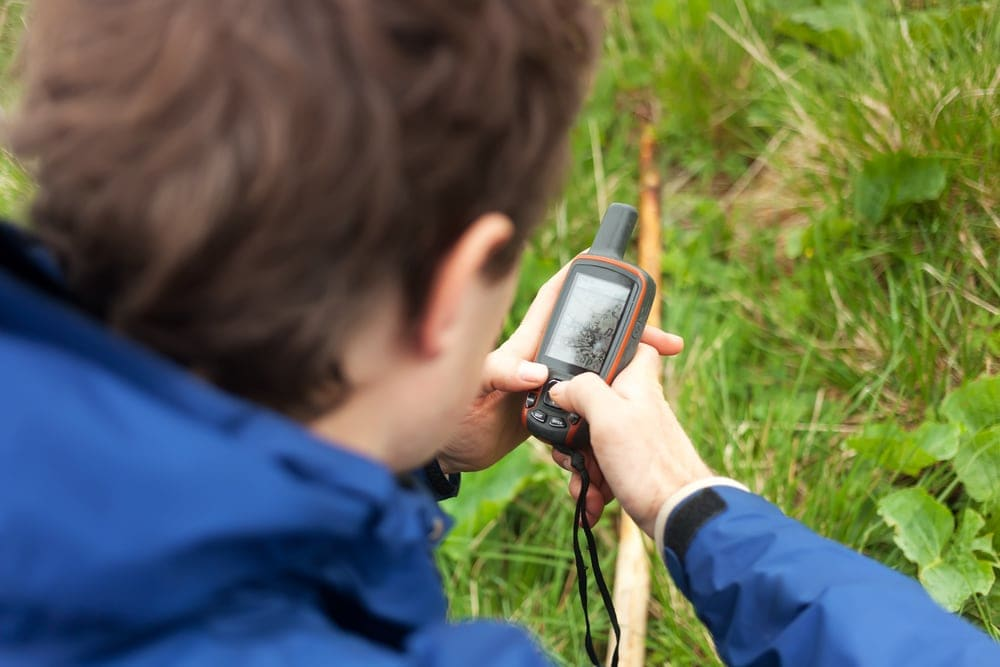 Man holding a satellite phone while hiking