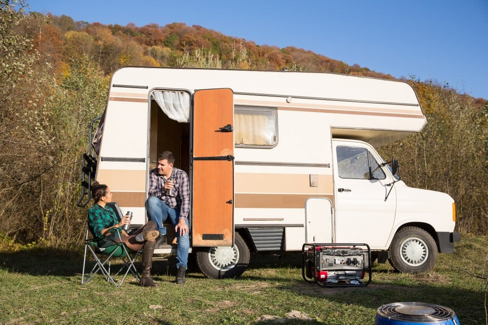 Camping portable generator outside a camper