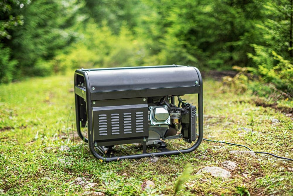 Black portable generator grounded for camping on the grass