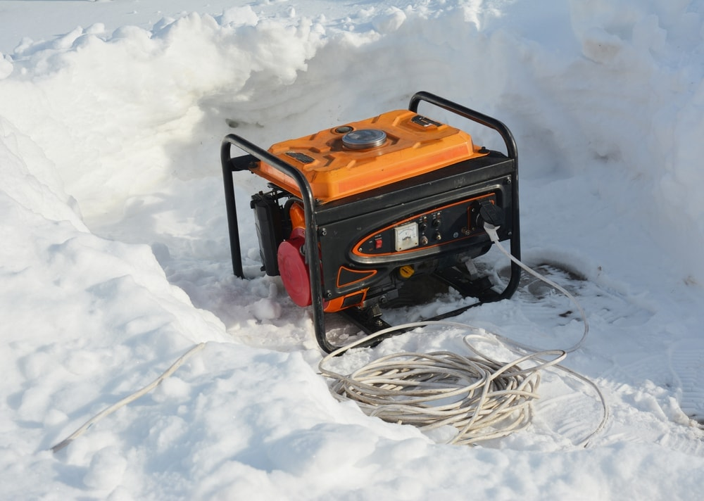 Generator on a snowy ground with a long coiled wire beside it