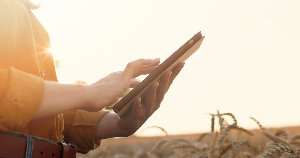 A woman holding a tablet while searching for internet while camping