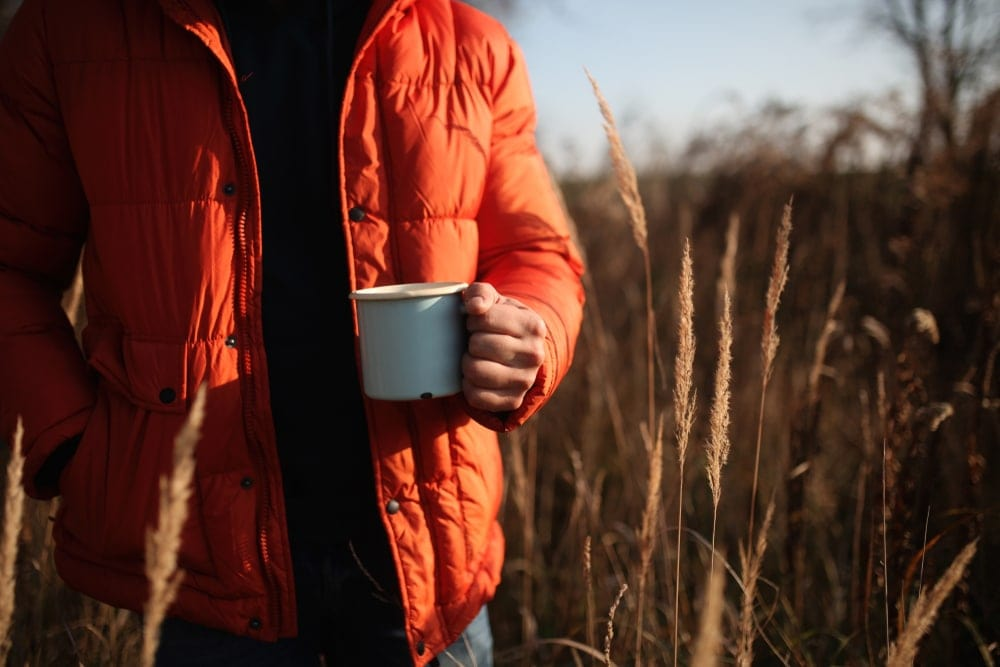 Man wearing a jacket holding a cup of coffee