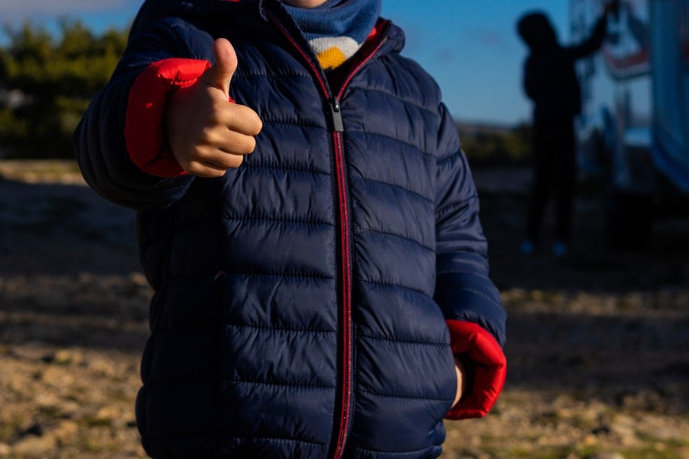A man wearing a blue outdoor jacket making thumbs up gesture