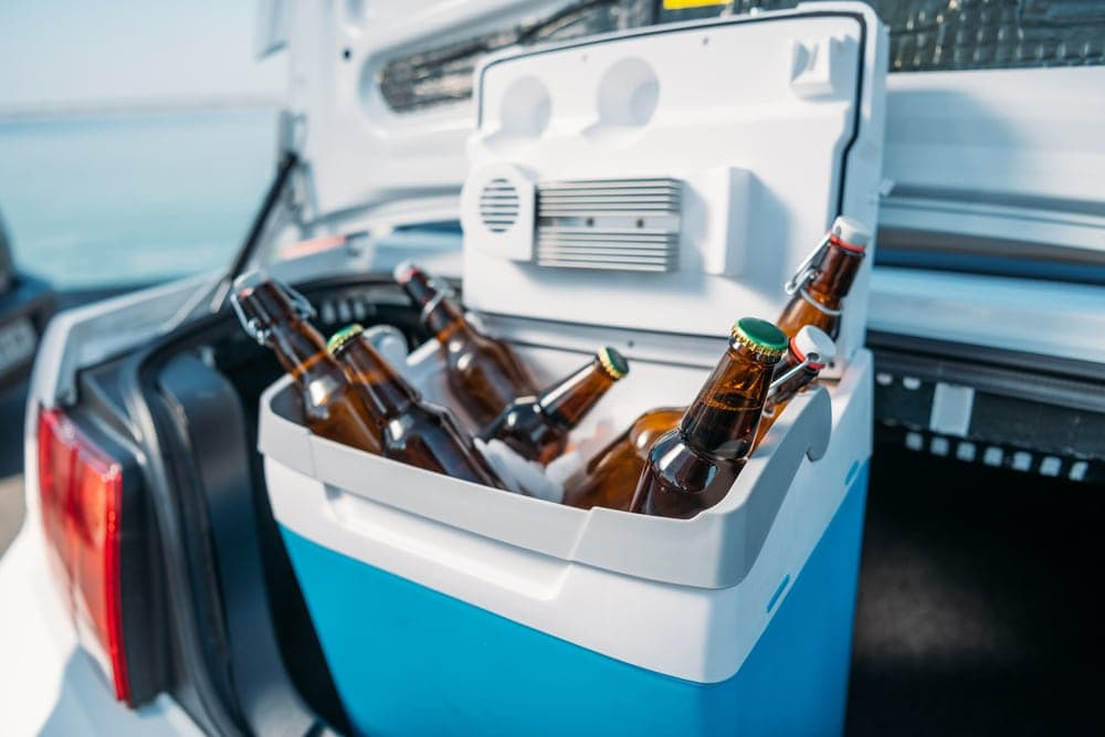Cooler in a car trunk filled with drinks and dry ice for camping