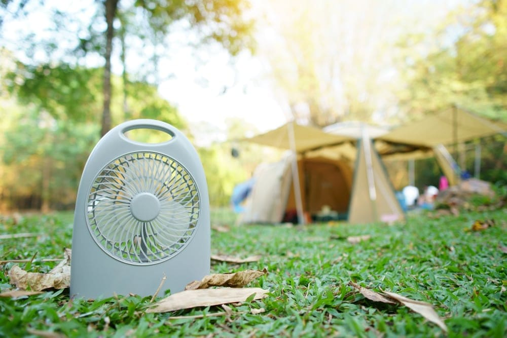 Mini fan on a grass with a blurred camping tent in the background