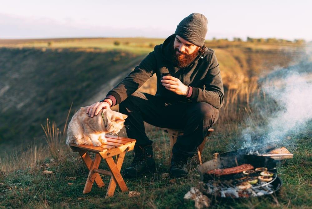 A man near a campfire touching the cat
