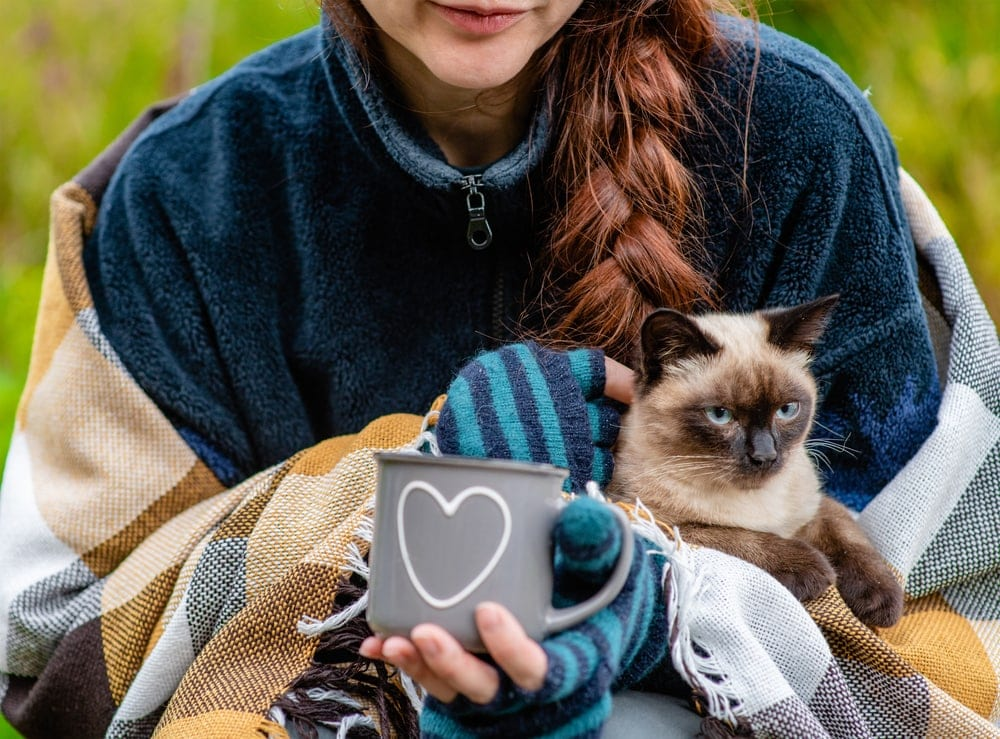 Woman carrying her cat while holding an enamel cup