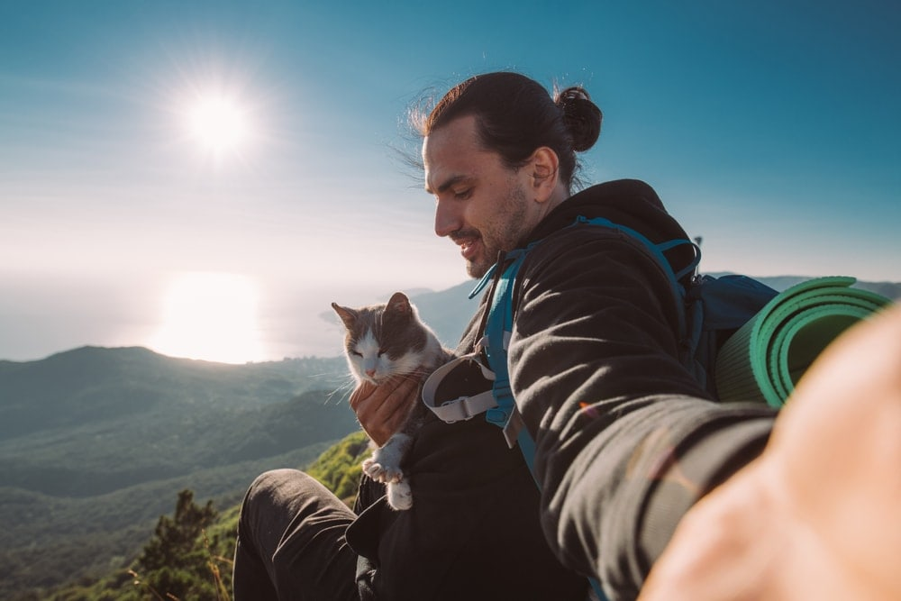 Man holding a cat on a backpacking trip