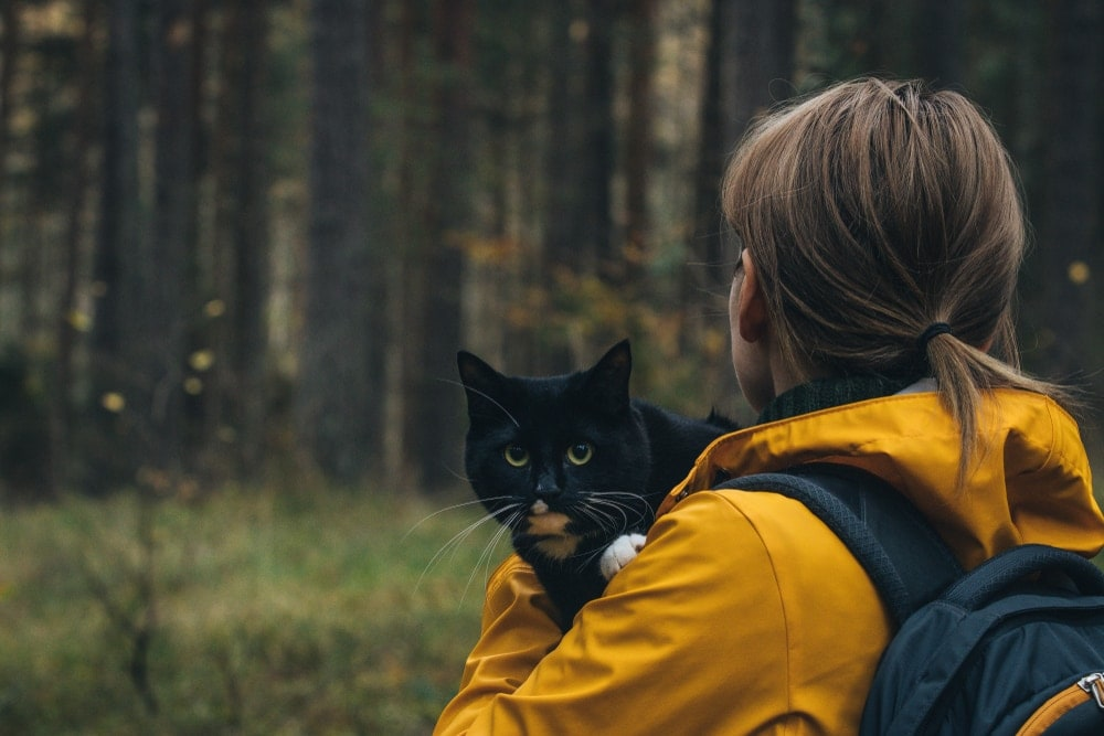 Woman carrying a black cat going into the woods