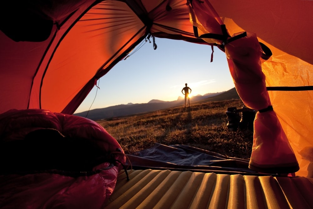Air mattress inside a camping tent and a man outside watching a sunrise
