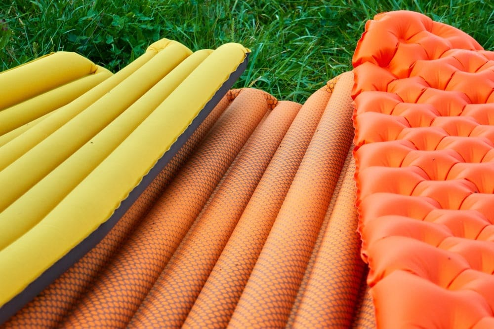 Three Inflatable camping mattresses in vibrant colors