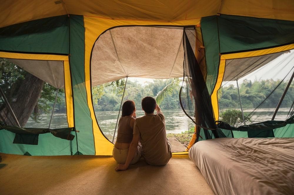 Couple sitting and talking near an air mattress inside a big tent