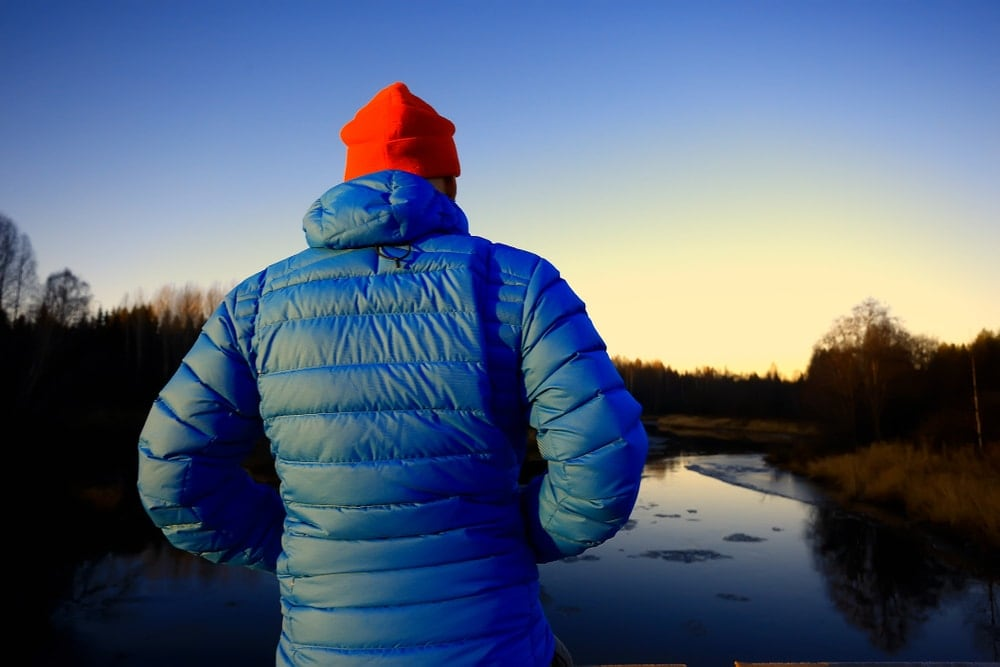 Man in a winter jacket looking over sunrise