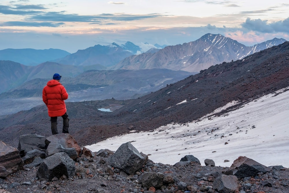 Hiker standing on top of the hill wearing a fjallraven winter parka