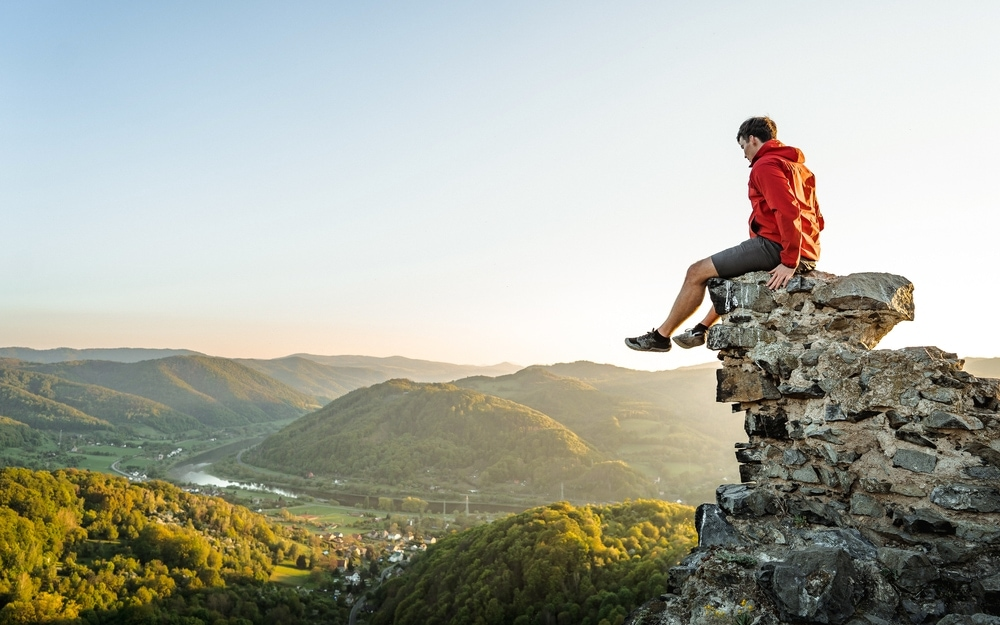 Hiker sitting on a cliff wearing a arcteryx jacket