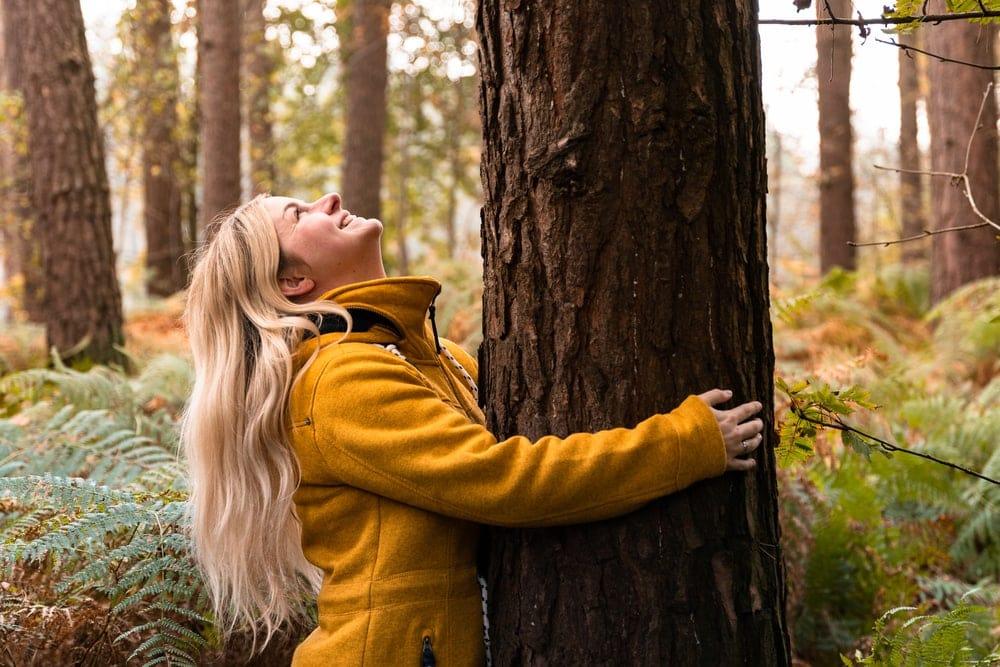 Woman wearing a fleece jacket hugging a tree in the woods