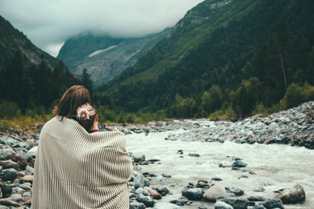 Couple wrapped in a cotton blanket looking at the river